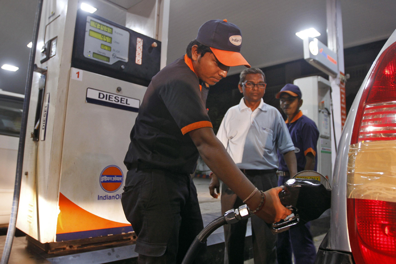 A worker fills a car with diesel at a fuel station in the western Indian city of Ahmedabad